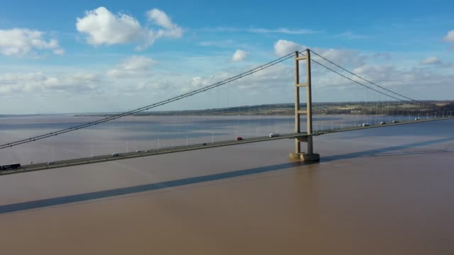 Aerial footage of The Humber Bridge, near Kingston upon Hull, East Riding of Yorkshire, England, single-span road suspension bridge, taken on a sunny day with a few white clouds in the sky. Aerial footage of The Humber Bridge, near Kingston upon Hull, East Riding of Yorkshire, England, single-span road suspension bridge, taken on a sunny day with a few white clouds in the sky. east stock videos & royalty-free footage