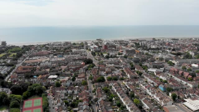 aerial footage of the town of worthing, large seaside town in england, and district with borough status in west sussex, england uk, showing typical housing estates and businesses on a bright sunny day - sussex occidentale video stock e b–roll