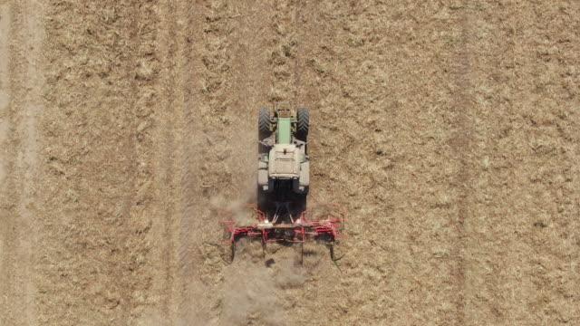 aerial: footage von traktor mit klingen schneiden trockene reste aus der ernte, um das feld vor dem düngen und säen vorzubereiten. - ausgedörrt stock-videos und b-roll-filmmaterial