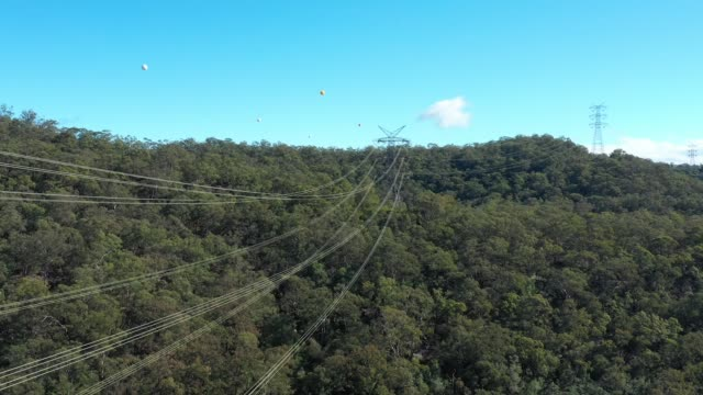 Aerial footage of transmission tower cables running across a river