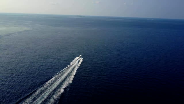 Aerial footage top view with motor boat at high speed cuts the waves while is leaving a long white trail. Conceptual video presentation for tourism. Expensive lifestyle and kind of leisure video