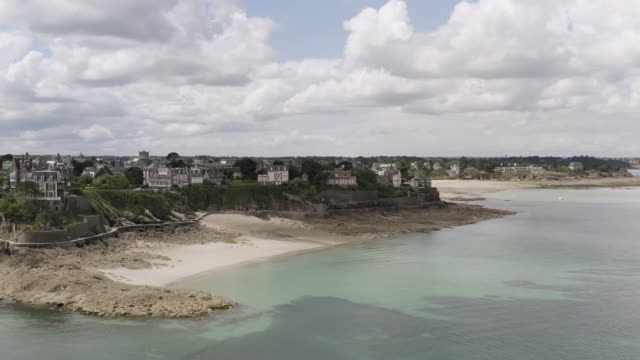 Aerial for the emerald coast located in the Dinard city, Brittany, France. Action. Breathtaking landscape with sea shore and cute cottages on blue cloudy sky background