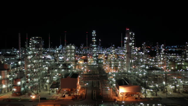 aerial forward into oil refinery industry real time - centrale elettrica video stock e b–roll