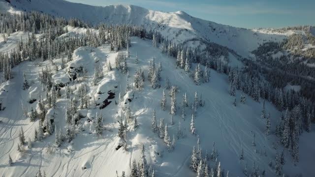 vídeos y material grabado en eventos de stock de aérea de drone hombre esquiador esquí de travesía en las montañas nevadas cuesta arriba en una línea. - viaje a canadá