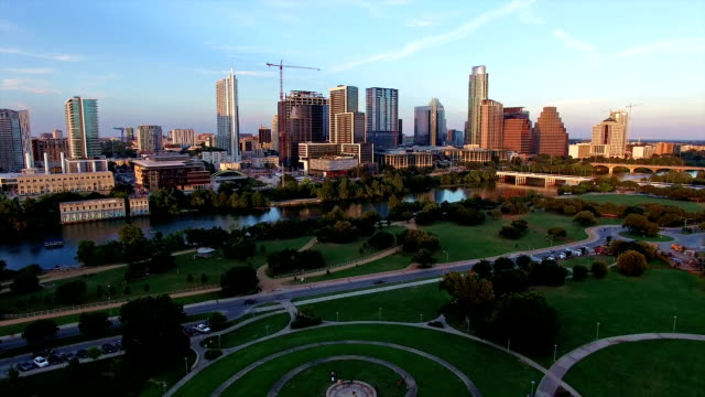 Aerial: Golden Sunset Over Austin Texas Skyline Cityscape View Aerial: Golden Sunset Over Austin Texas Skyline Cityscape View with a perfect golden reflection off the high skyscrapers and office buildings along Town Lake post modern architecture stock videos & royalty-free footage