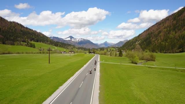 vídeos de stock, filmes e b-roll de aéreo: grupo de motociclistas motor em estrada curva montando nos alpes austríacos - tyrol state austria