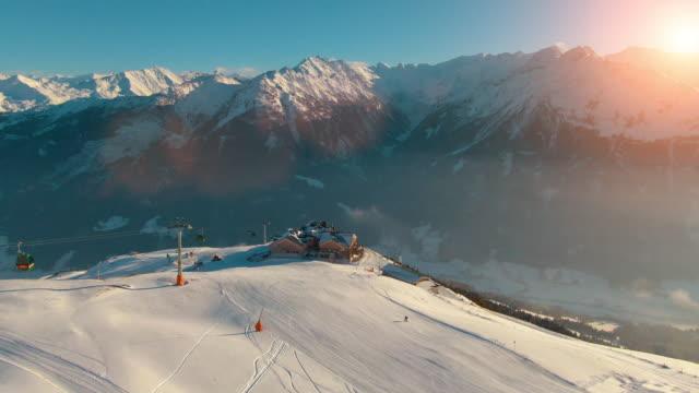 vídeos y material grabado en eventos de stock de helicóptero aéreo filmado por un tranquilo paisaje rural de montaña, picos de montaña cubiertos de nieve y paisaje de estación de esquí en los alpes austriacos en un día soleado por la tarde - austria