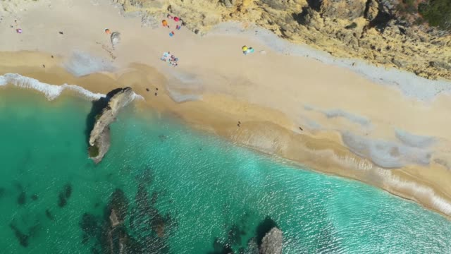 Aerial High Angle view a sandy beach line full of bathers and colorful umbrellas
