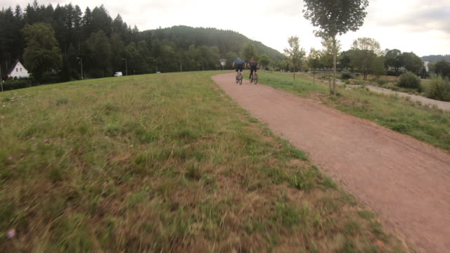 aerial high speed drone shot of mountain bikers near a forest and river - percorso per bicicletta video stock e b–roll