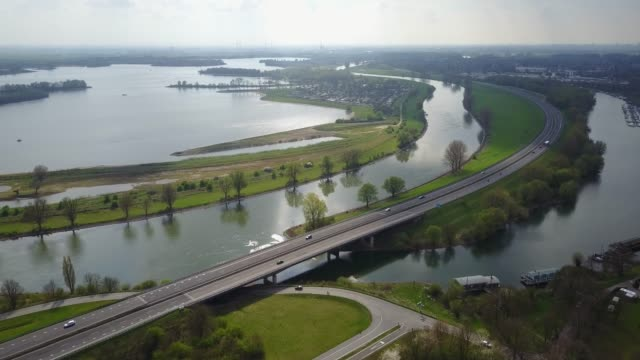 aerial: highway beside river ijssel in the netherlands with traffic - dutch architecture stock videos & royalty-free footage