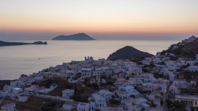 aerial hyper lapse above typical greek village at sunset overlooking the aegean sea, cyclades, greece - morze egejskie filmów i materiałów b-roll