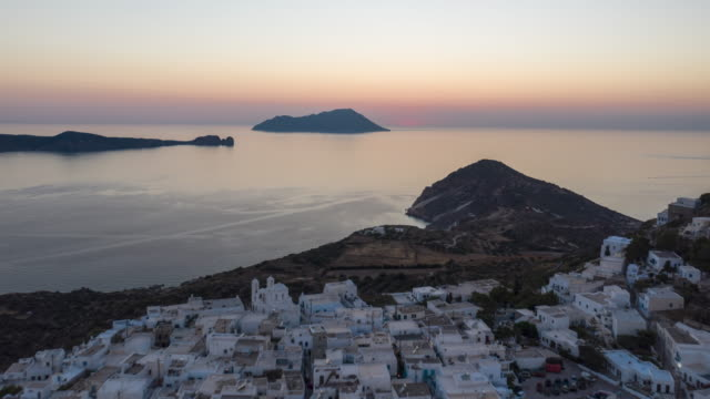 aerial hyper lapse moving time lapse above typical greek village at sunset on milos, greece island with ocean view - morze egejskie filmów i materiałów b-roll