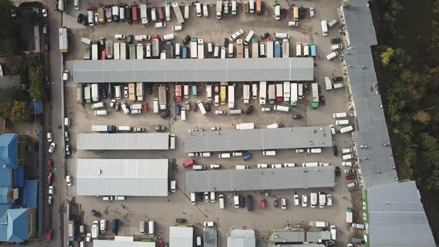 Aerial hyper lapse (hyperlapse - time lapse) of a large logistics park with a warehouse - loading hub. Semi-trucks with freight trailers standing at the ramps for loading/unloading goods