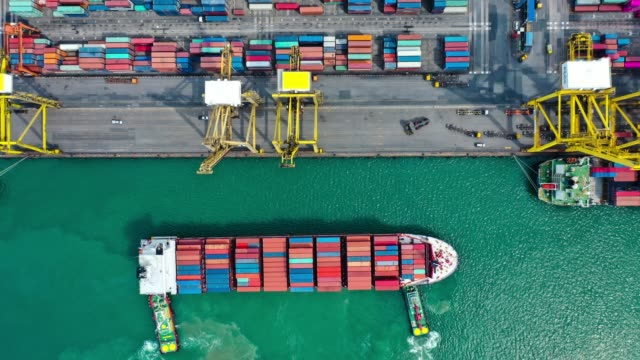 vídeos de stock e filmes b-roll de aerial hyper lapse of container ship in to the port at southeast asia - docas