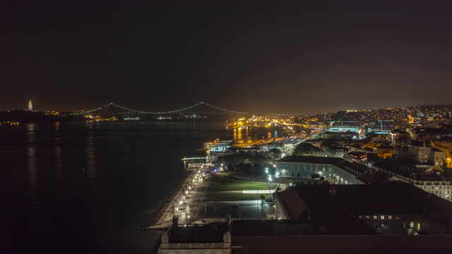 Aerial hyperlapse of Lisbon city center at night. Tourist attractions in city harbor in Portugal