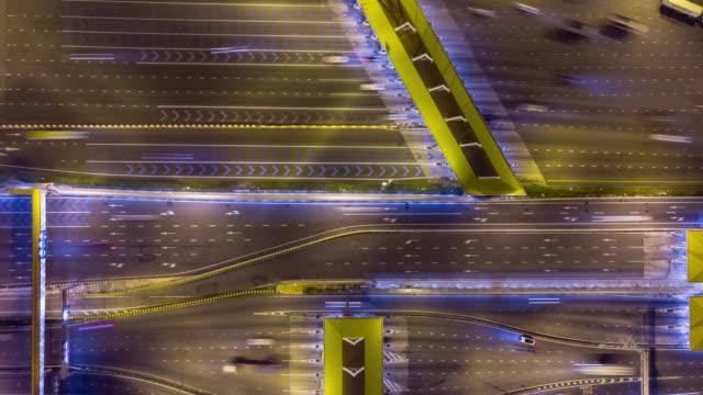 iperlapsia aerea sul casello o ingresso autostradale di notte con molti veicoli che attraversano il gate tariffario. colpito da un drone ad alta risoluzione. - fare video stock e b–roll