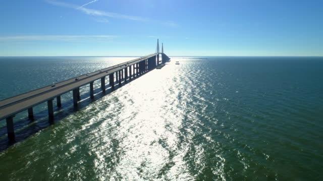 aerial hyperlapse sunshine skyway bridge tampa bay florida - побережье мексиканского залива сша стоковые видео и кадры b-roll