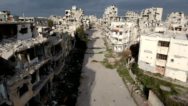 Aerial in the street of Syria under a cloudy sky Destroyed houses in Syria since the war. Buildings with no people in a damaged city. Aerial view with a drone of Aleppo destroyed because of terrorism. War years in Syria. Streets ravaged because of bombing. old ruin stock videos & royalty-free footage