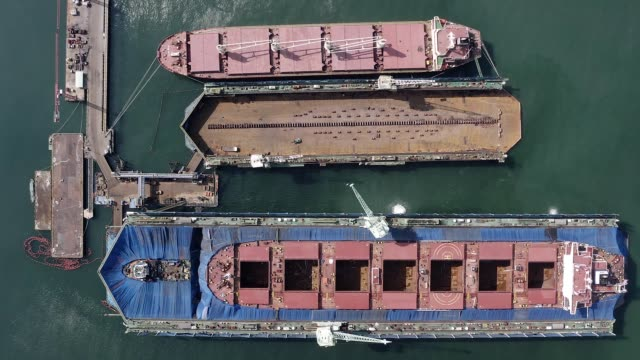 Aerial landscape cargo ship in industrial shipyard. Sea ships standing on parking lot in dockyard drone view.