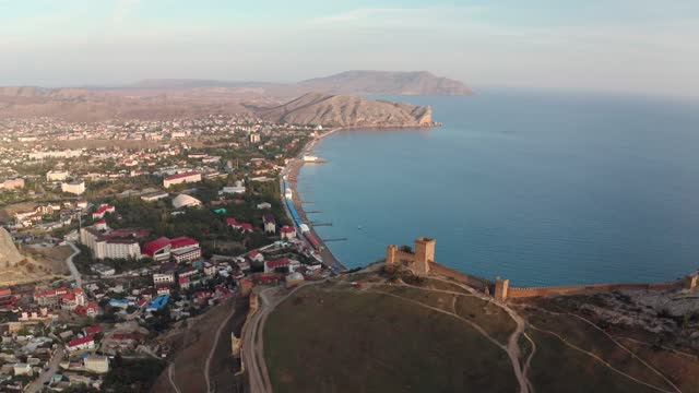 Aerial landscape Genoese fortress on mountain top, Black Sea shore and Sudak city. Ancient fortress on modern resort city architecture background from flying drone