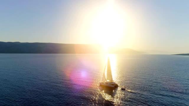 Aerial Long Shot of a Sailing Catamaran Yacht with Raised Sails Traveling Through Open Seas. Sun Shines with Coastal Hills Visible.