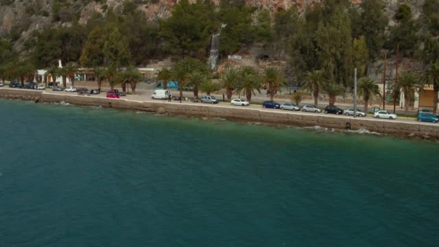 Aerial - Loutraki - Greece, backward revealing of a coastal road with palm trees and a waterfall video