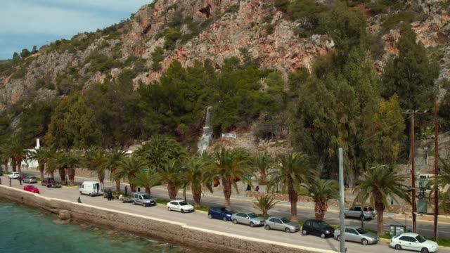 Aerial - Loutraki - Greece, forward take of a coastal road with palm trees and a waterfall video