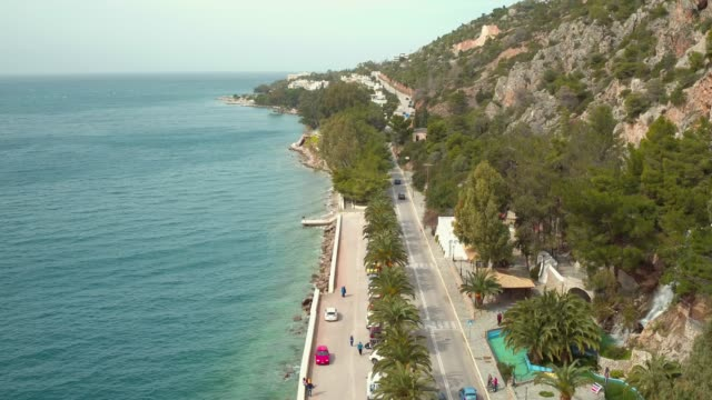 Aerial - Loutraki - Greece, steady shot from above of a coastal road with palm trees and a waterfall video