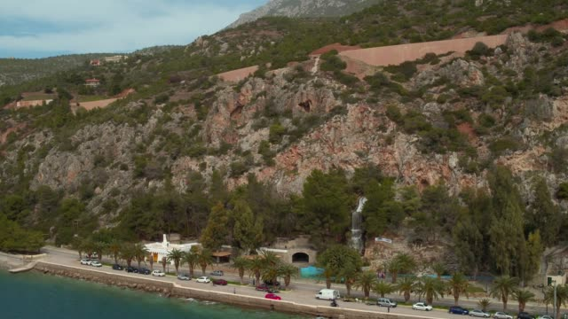 Aerial - Loutraki - Greece, vertical downward revealing of a coastal road with palm trees and a waterfall video