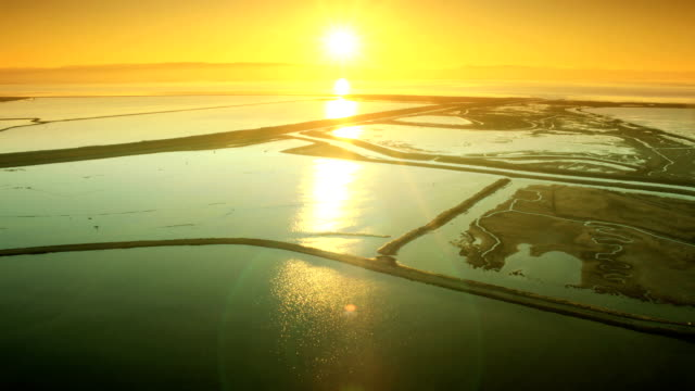 Aerial low angle view of natural mineral rich salt ponds Aerial low angle view of natural mineral rich salt water ponds at sunset marsh stock videos & royalty-free footage