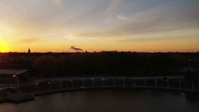 vídeos de stock, filmes e b-roll de a antena baixando em direção a um parque à beira-mar no rio em toledo, ohio, enquanto o sol laranja brilhante sobe sobre o horizonte iluminando o céu e a fumaça vomitando de chaminés no horizonte. - sol nascente horizonte drone cidade
