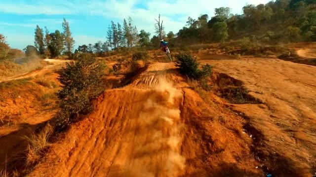 Aerial: Man jumping on motocross bike. Slow motion.