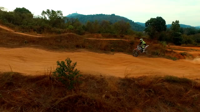 Aerial: Man riding a bike on motocross track. video