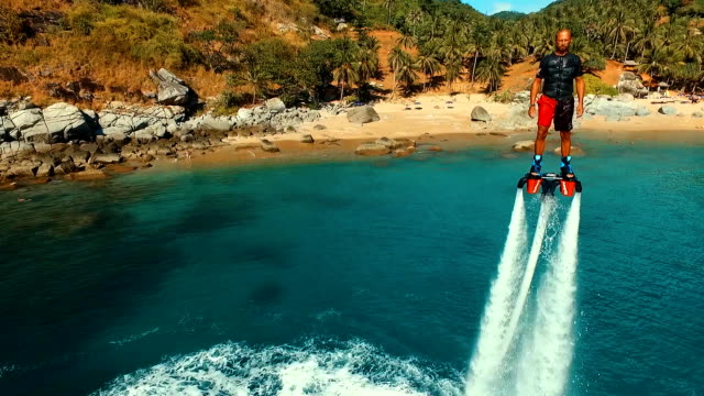 Aerial: Man standing over the water on flyboard near the beach. video