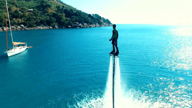 aerial: man standing over the water on flyboard. - phuket video stock e b–roll