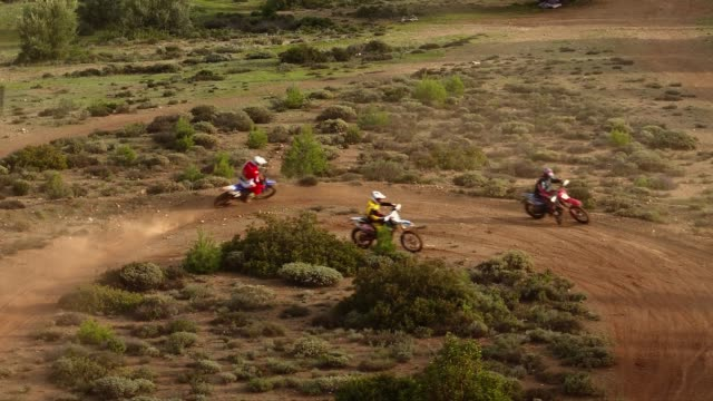 Aerial, motocross sports and practice at the forest, 3 motocross athletes performing a right turn with their motorbikes video