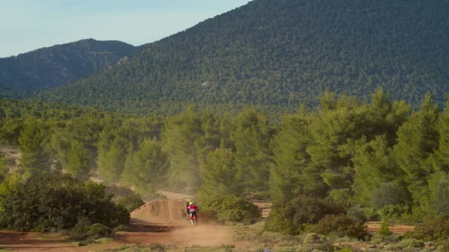 Aerial, motocross sports and practice at the forest, a motocross athletes performing a jump with his motorbikes, shooting from behind video