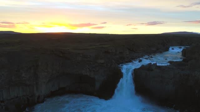 vídeos y material grabado en eventos de stock de cascada de 4 k aérea drone mover flyover aldeyjarfoss escena de amanecer, verano de islandia - basalto