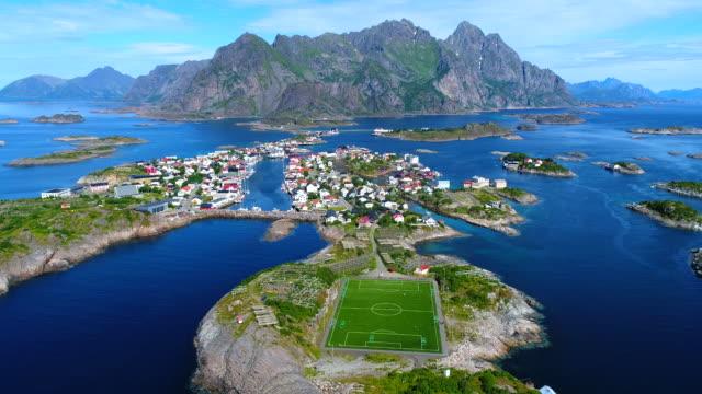 4k hava film köprü henningsvaer köyü genel futbol alanında lofoten adası, norveç - mountain top stok videoları ve detay görüntü çekimi