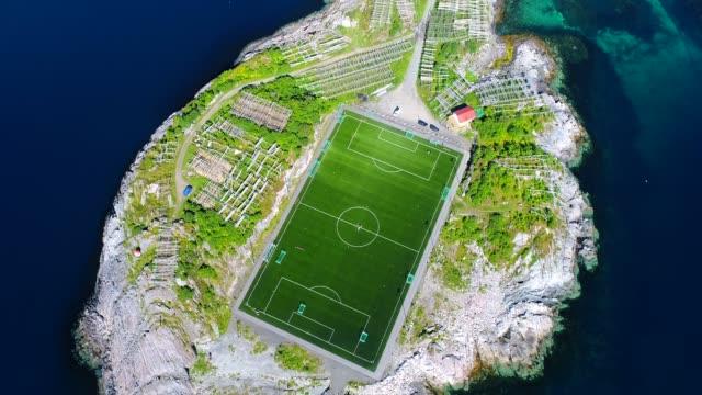 vídeos de stock e filmes b-roll de 4k aerial movie flyover henningsvaer village public football field in lofoten island, norway - lofoten