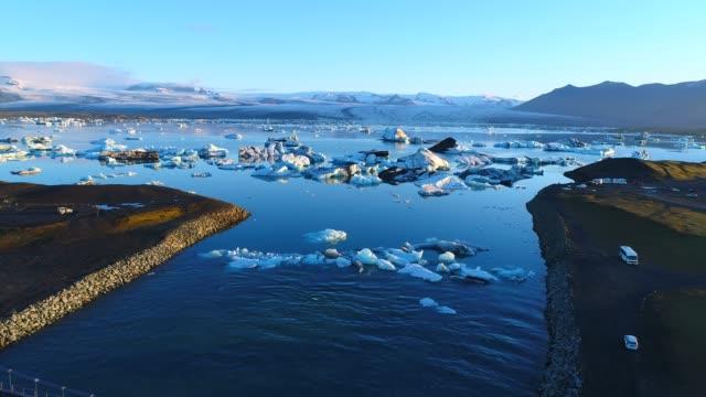 4k воздушный фильм flyover над ледником куски лагуны , jokulsarlon в исландии - ледник стоковые видео и кадры b-roll