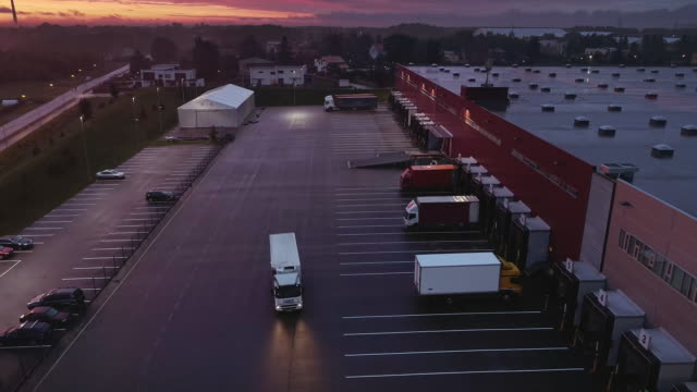 Aerial Moving Footage with Multiple Loading Stations with Lorry Trucks at an Industrial Warehouse of Logistics Building. Evening Twilight Sunset with Light Clouds and Pink Hue. Aerial Moving Footage with Multiple Loading Stations with Lorry Trucks at an Industrial Warehouse of Logistics Building. Evening Twilight Sunset with Light Clouds and Pink Hue. warehouse aerial stock videos & royalty-free footage