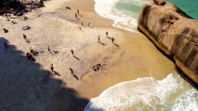 Aerial moving shot of cariocas playing on sandy beach in Rio de Janeiro, Brazil video