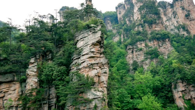 Aerial near vertical high cliff pillars and columns in mountains of Zhangjiajie Aerial near vertical high cliff pillars and columns in the mountains of Zhangjiajie Park. Rock formations destroyed by corrosion. Tropical evergreen forest in grows on the hillside. sandstone stock videos & royalty-free footage