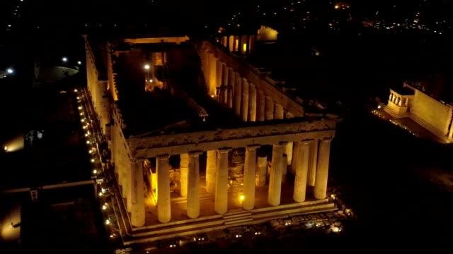 vídeos de stock, filmes e b-roll de vídeo de noite aérea da antiga icônico acropolis hill e o partenon à noite, o centro histórico de atenas - cultura grega