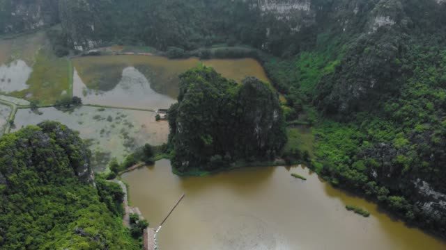 Aerial: North Vietnam karst landscape at sunset, drone view of Ninh Binh region