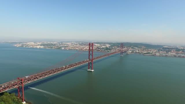 vídeos de stock e filmes b-roll de aerial of 25th of april bridge and christ the king monument - cristo rei lisboa