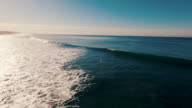 istock Aerial of a beautiful sunrise sparkling off the ocean as a surfer paddles out into the lineup and a big wave crashes over his head, all glowing in the early morning light. 494785972