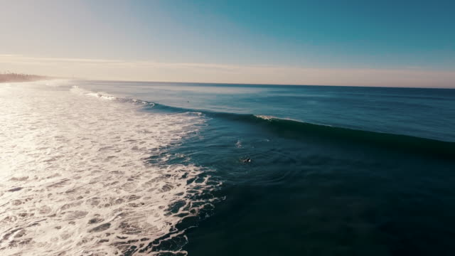 Aerial of a beautiful sunrise sparkling off the ocean as a surfer paddles out into the lineup and a big wave crashes over his head, all glowing in the early morning light. video
