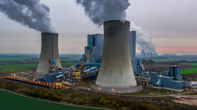 Aerial of a coal fired power station Flight around a large coal fired power station wit two giant cooling towers. An other power plant is in the background. Moody sky at dusk. The industrial building is already illuminated. North Rhine Westphalia - Germany coal stock videos & royalty-free footage